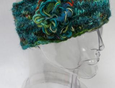 Teal knit wool headband with lime, orange & white though-out & large loopy wool flower of same colors attached to side