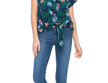 Model wearing short sleeve pullover blouse with ties at front waist - deep blue & green leaves & flowers print