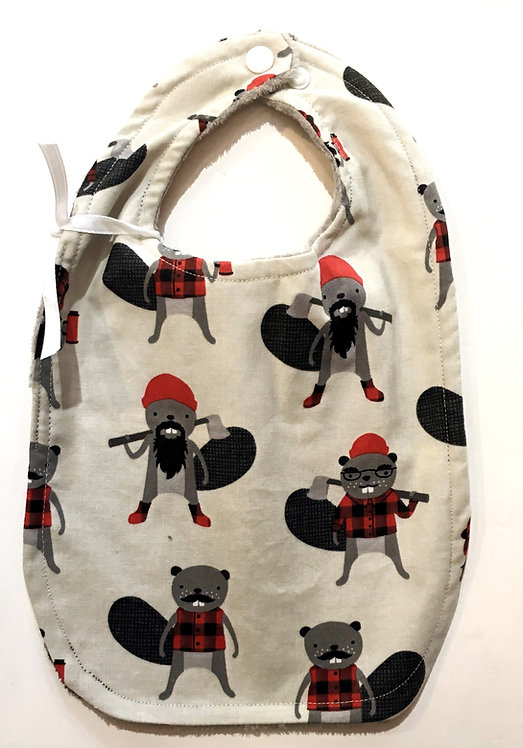 Oval shaped white cotton bib with print of beavers with axes dressed as lumberjacks in red & black plaid clothes