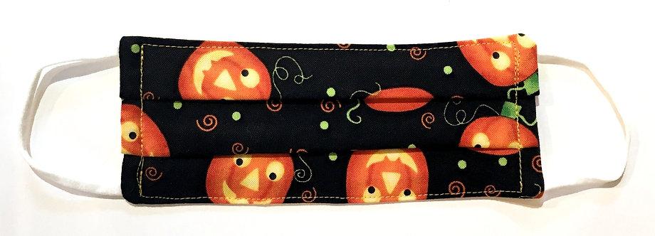 Tiny black cotton mask laid flat with orange smiling carved pumpkins print