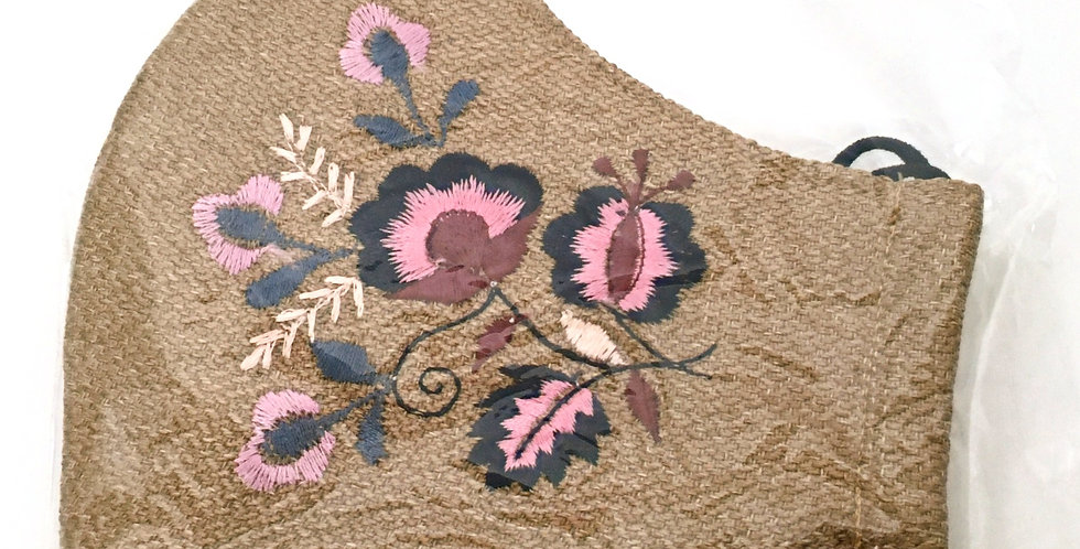 Side view of folded ochre embroidered mask with pink, navy, gray & cream floral design