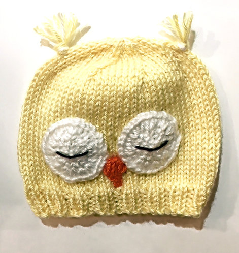 Knit infant hat yellow with 2 sleeping owl eyes & beak stitched on-ear tassels at top