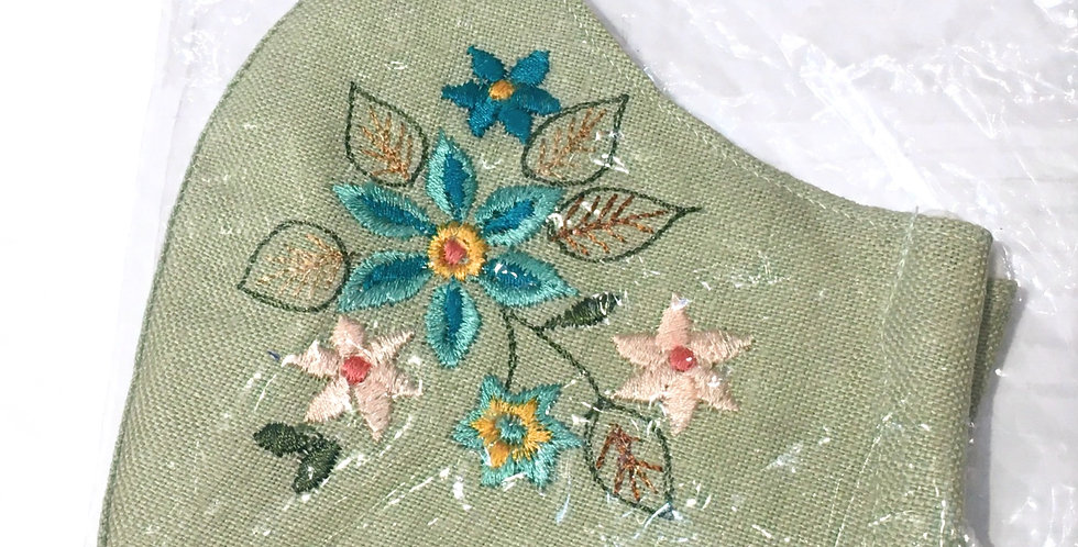 Side view of folded pale green embroidered mask with turquoise, yellow & pink flowers with green & brown veined leaves