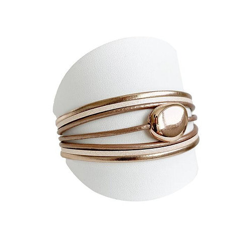 Angled side view of nude leather multi strand bracelet with shiny oval shaped metal center