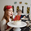 Girl with red superhero mask pushed up on head blows our metallic candles on birthday cake