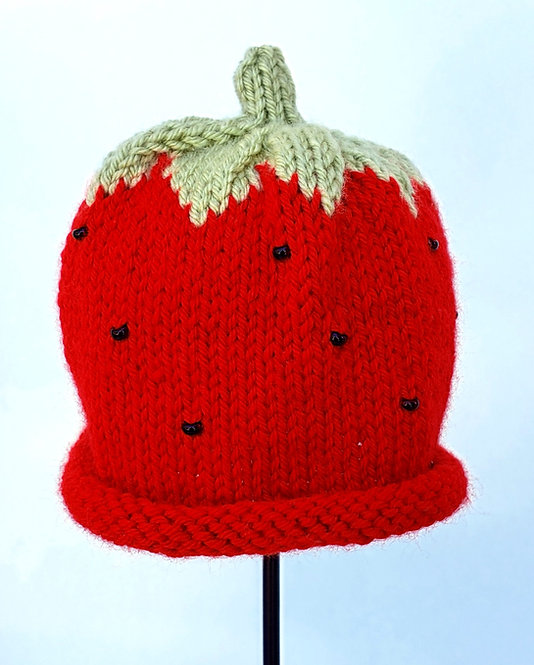 Bright red knit infant's hat on stand with rolled brim & green leafy top & stem, beads sewn on to look like strawberry seeds
