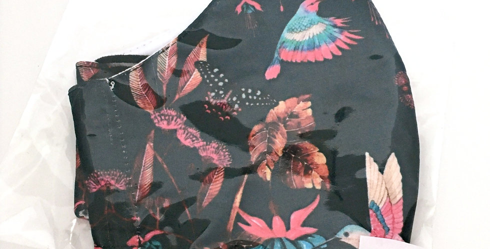 Side view of folded black mask with fuchsia, turquoise, rust  hummingbird print