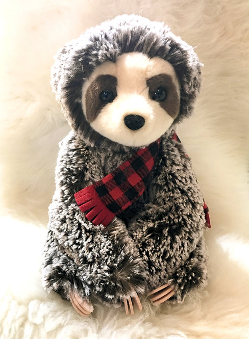 Brown & white plush toy sloth with red & black check scarf in seated position with paws tucked in