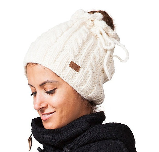 White cable knit hat with opening for ponytail, wool drawstring tied in bow at side