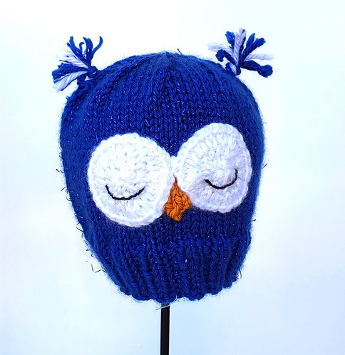 Bright blue Hand Knit Infant Hat with big white sleeping owl eyes, orange beak and ear-like tufts of wool on top