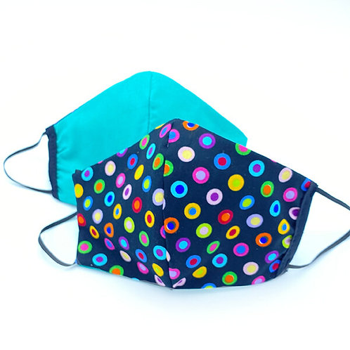 Two cotton reversible masks showing colorful polka dots on navy background one side, solid turquoise the other