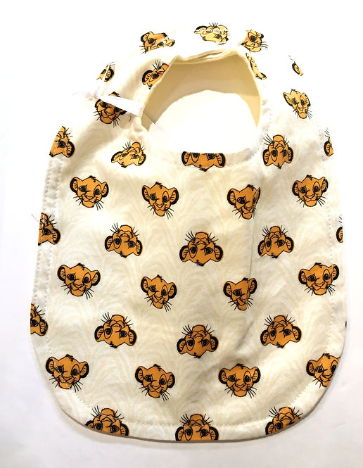 Pale yellow oval shaped cotton bib with print of small gold lion's heads