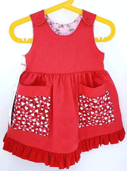 Handmade child's sleeveless Red / Pink Reversible Dress, solid red with pink & white hearts print on 2 pockets, ruffled hem