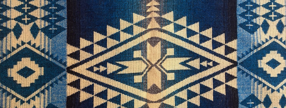 Close up of ivory & blue geometric patterned blanket