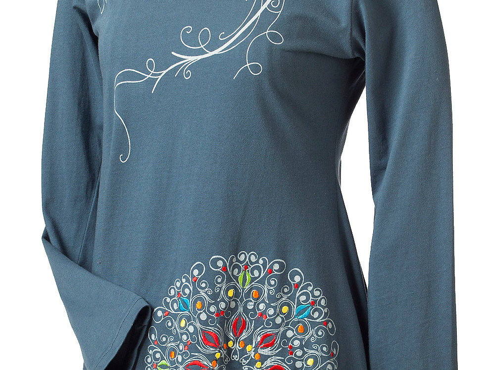 side view-teal round neck top long sleeve gray swirling line across chest & shoulder-colorful round mandala print left hem