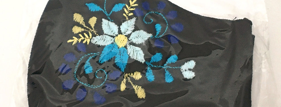 Side view of folded navy embroidered mask with light blue &teal flower surrounded by indigo, teal & cornsilk leaves & stems