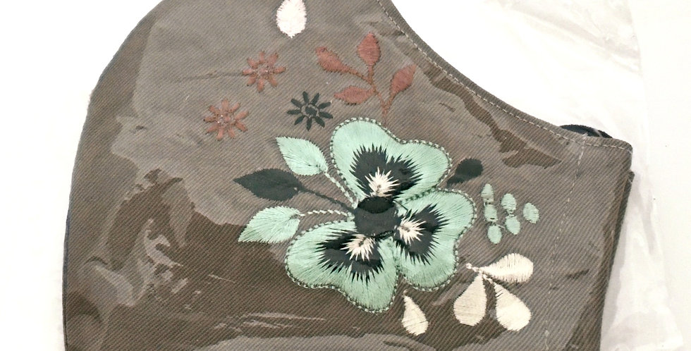 Side view of folded gray embroidered mask with pale turquoiseflower and dark green, rust and cream accents