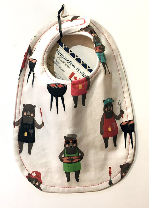 white oval-shaped cloth baby bib with brown bears dressed in aprons with BBQ's & utensils