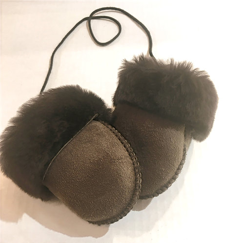 tiny thumbless sheepskin mittens with cuffs turned down to show fleecy inside, attached by a string