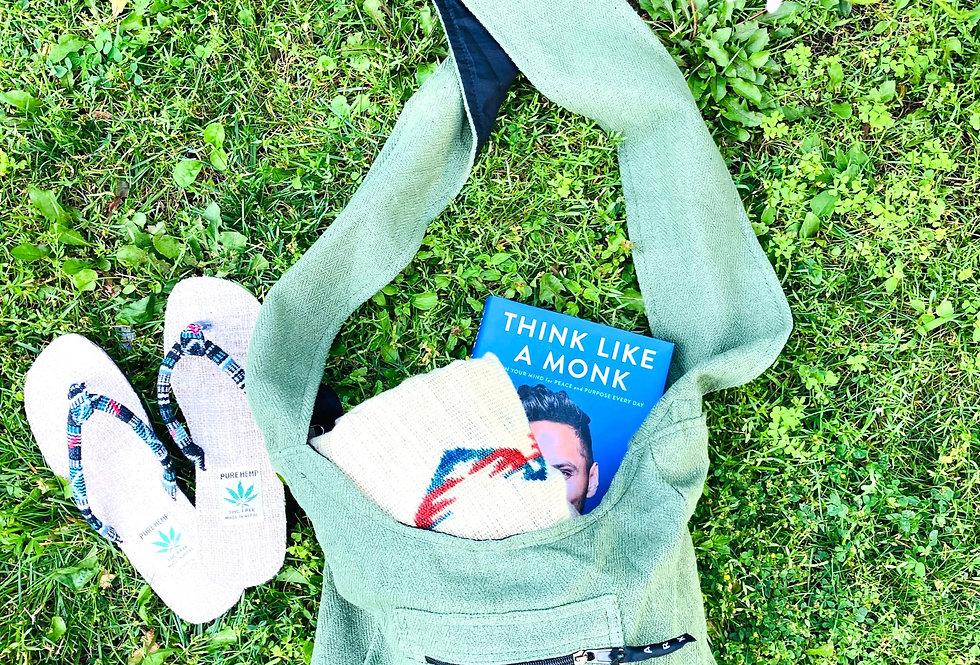 Green Shiloh bag holding folded blanket beside pair of hemp sandals