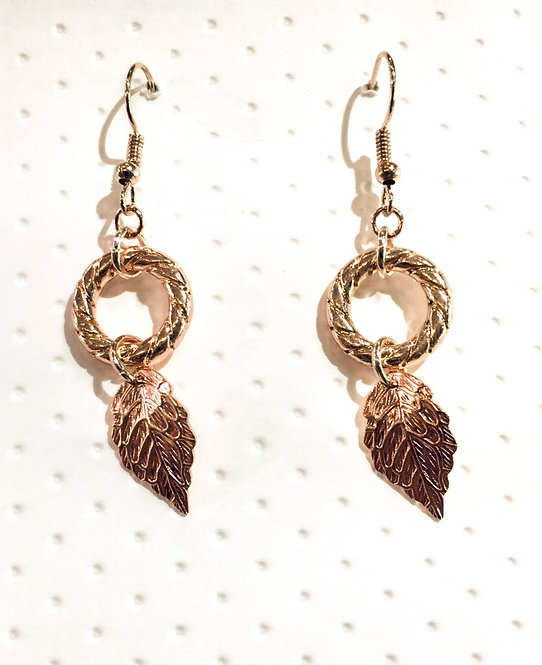 Pair pf rose gold colored earrings with delicate leaf hanging from ornate hoop