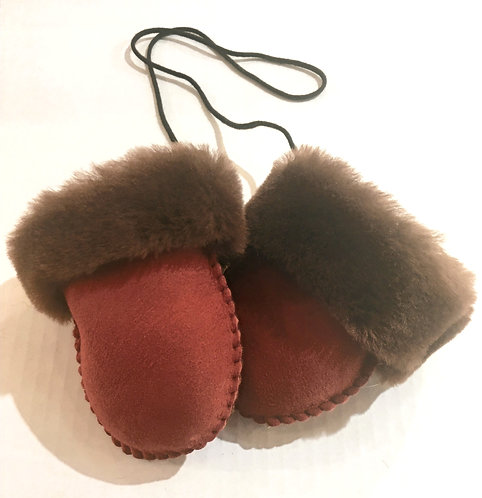 pair of tiny red thumbless sheepskin mittens with cuffs turned down to show brown fleece interior