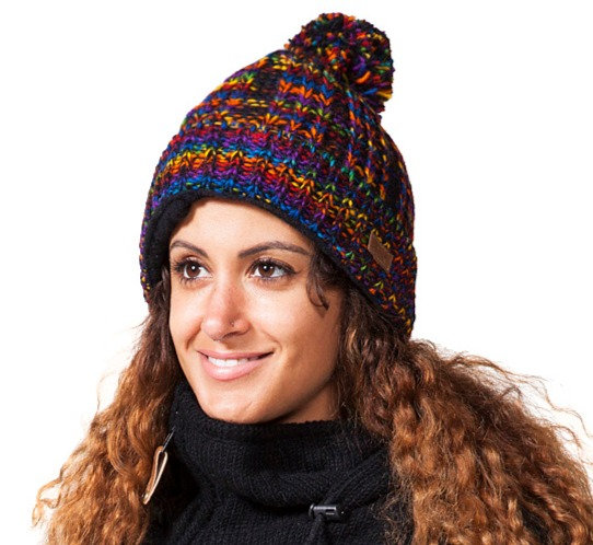 Model wearing blended rainbow striped wool knit hat with pompom