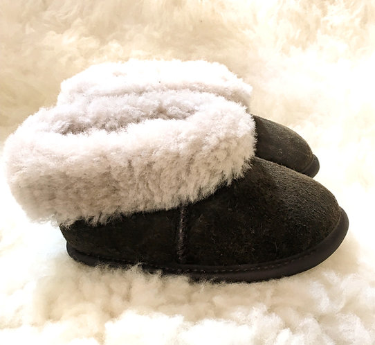 Right view of small pair of brown sheepskin slippers with natural white fleece interior showing on turned back cuffs