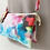 Close up of mannequin with mixed-color small rectangular purse hanging from shoulder