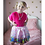 Little girl standing on bed wearing pink full short skirt covered in multi-colored large sequins