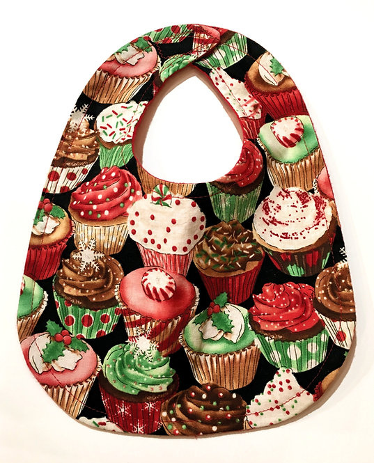 black oval-shaped cloth baby bib with decorated frosted cupcakes in red, white & green