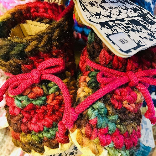 Front view of babies' crocheted wool slippers in blended shades of burgundy, green, brown and gold on display