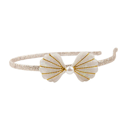 Narrow gold headband with bow accent fashioned from 2 pearlescent shells striped with gold and pearl at the center
