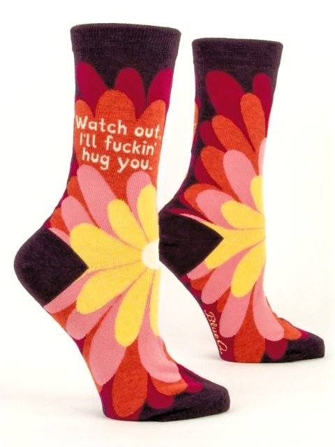 side view of socks with big yellow-pink-peach-magenta daisy on top-black heel-toe-cuff-text 'Watch out, I'll fucking hug you""