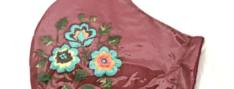 Side view of folded merlot embroidered mask with light turquoise flowers witholive green & yellows