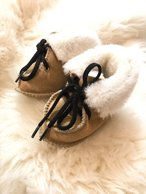 Angled side view of pair of baby size sheepskin slippers with natural white interior fleece cuffs & black laces