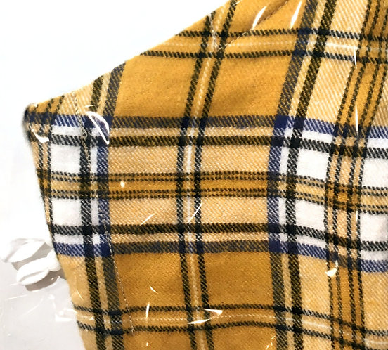 Close up of yellow & black plaid print mask folded in half in plastic