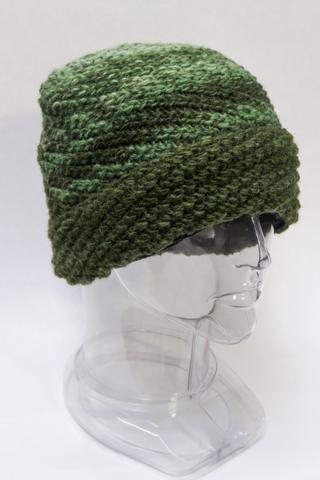 Green wool hat knit in diagonal rib pattern, brim folded back into a cuff