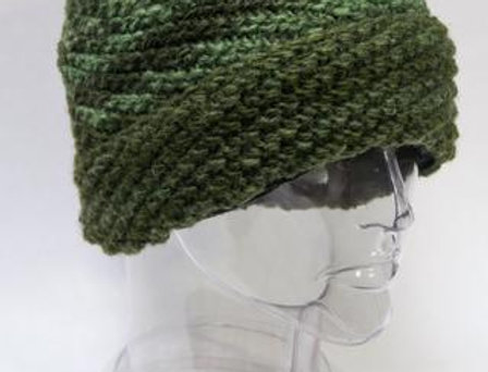 Green wool hat knit in diagonal rib pattern, brim folded back into a cuff