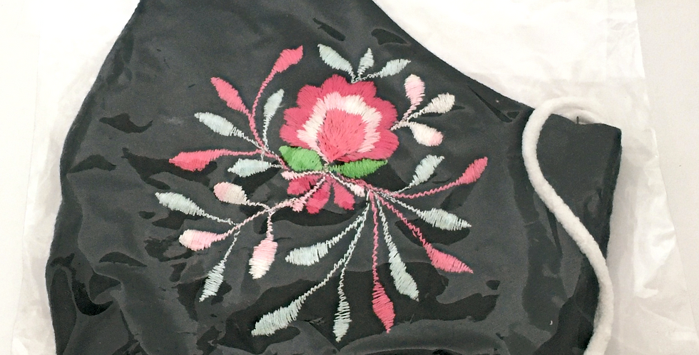 Side view of folded navy embroidered mask with magenta, pale pink, light blue & spring green floral pattern