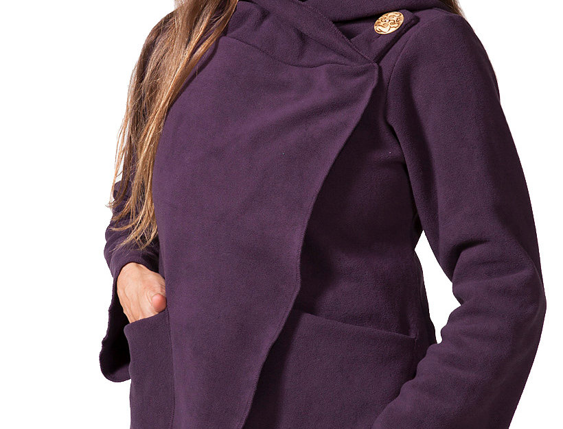 Model wearing purple fleece jacket-long bell sleeve-hood-wrap over front with large button closer on one shoulder