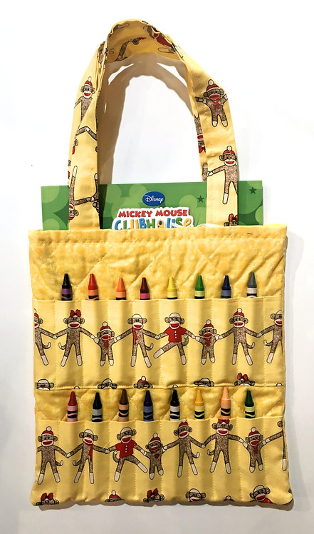 Flat rectangular yellow cotton tote bag holding a crayon book & 16 slots for crayons on the front