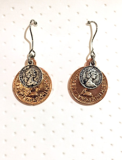 Rose gold colored earrings small silver antique coin in front of larger gold coin