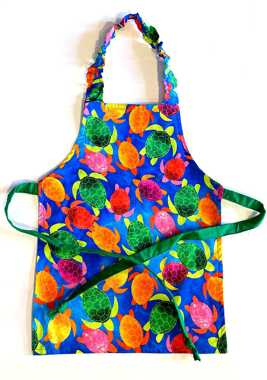 Front view of child's apron - red, green, orange & yellow turtles on blue background