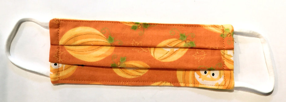 Tiny orange cotton mask laid flat with light orange pumpkins print, some carved, some not