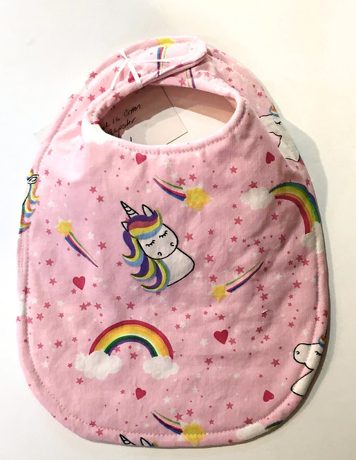 pink oval-shaped cloth baby bib with  rainbows and unicorns with rainbow manes & dark pink stars all over