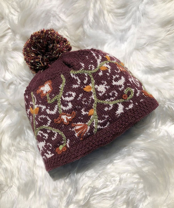 Burgundy knit wool pompom toque with white pattern & green & gold embroidery