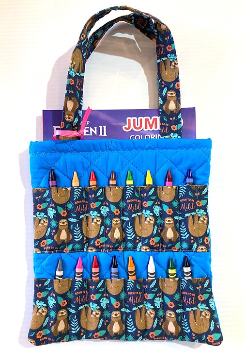Flat rectangular blue & black cotton & black tote bag holding a coloring book & 16 crayons in slots on the front