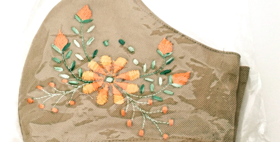 Side view of folded embroidered cafe-latte cotton mask - gold daisy surrounded by delicate nectarine buds & soft green leaves