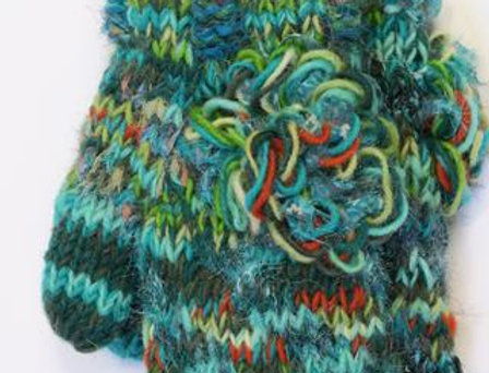 Mostly teal knit wool mitts with lime, orange & white though-out & large loopy wool flower of same colors attached to back